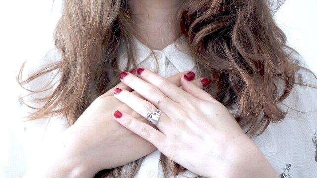 女性の胸元と手